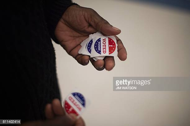 A polling manger holds 'I Voted' stickers as she wait for people to cast their ballots in the Republican presidential primaries at Moultrie Middle...