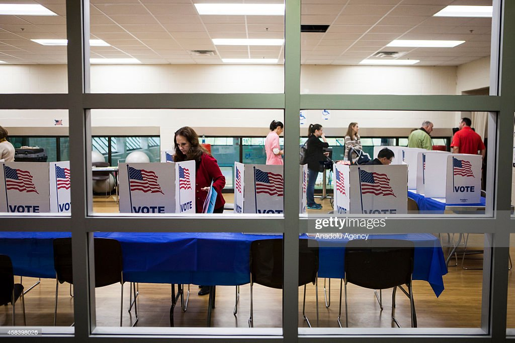 A polling official straightens up the voting booths at a polling station during the US midterm elections in McLean Virginia on November 4 2014