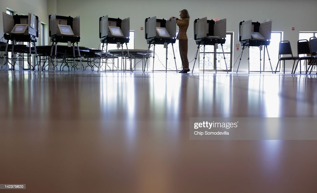 A polling place worker maintains digital voting machines during the presidential primary election at Saints Peter Paul Antiochian Orthodox Christian...