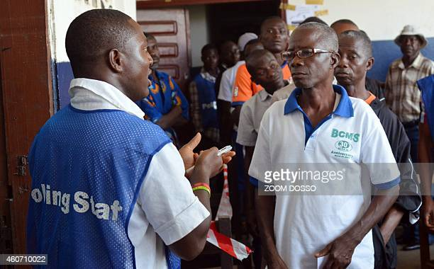 A polling station agents gather at a polling station in Monrovia during parliamentary elections on December 20 2014 Liberians began voting on...