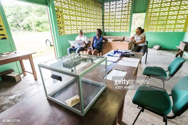 Polling station attendants wait for voters at a polling station in Trou Poissons French Guiana during the second round of the French presidential...