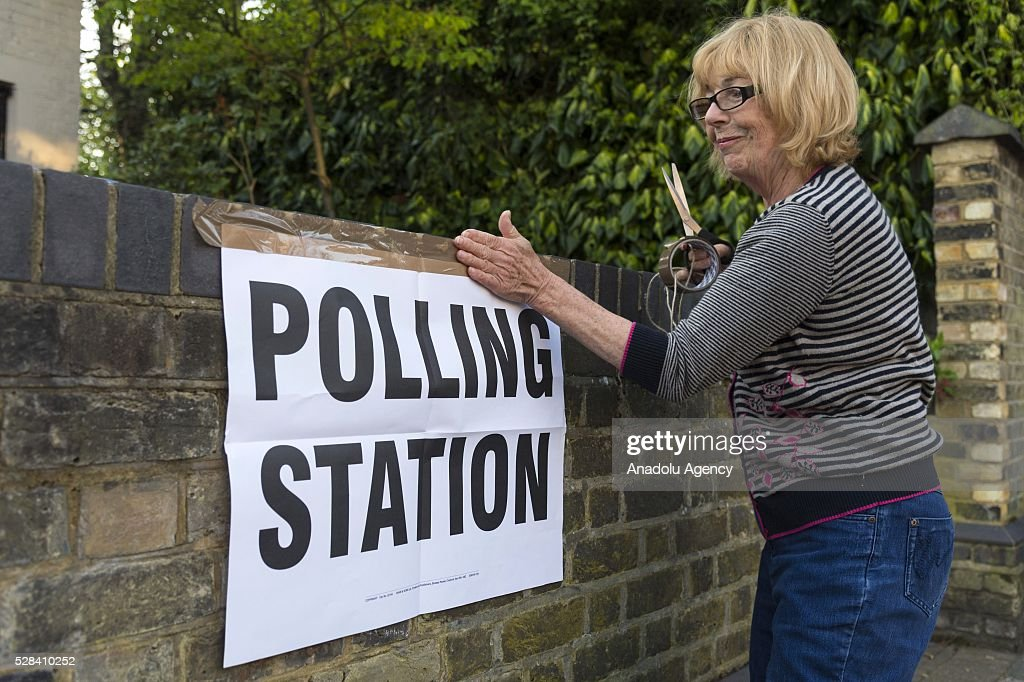 Polling station clerk hangs a poster, reading 'polling station' on a wall of Kitson Hall polling station during the London Mayoral Election in London, United Kingdom on May 05, 2016.