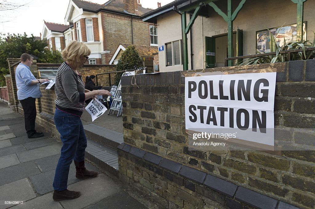 Polling station clerk hangs posters, reading 'polling station' on a wall of Kitson Hall polling station during the London Mayoral Election in London, United Kingdom on May 05, 2016.