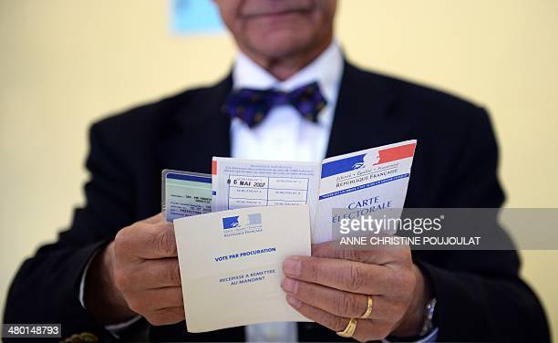 A polling station official checks the ID card of a voter during the first round of the French municipal elections in Marseille on March 23 2014 The...