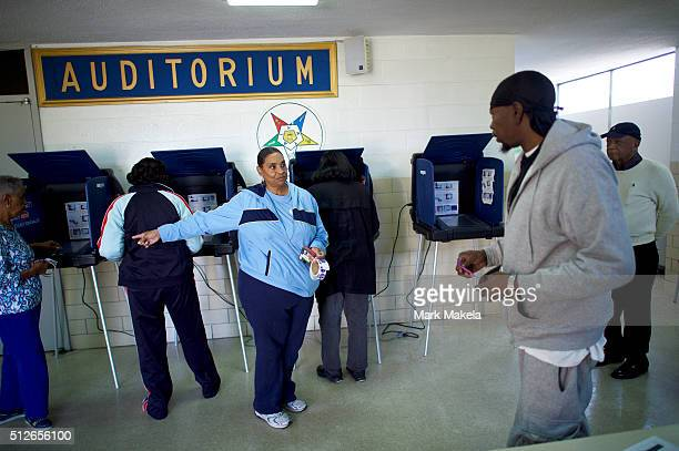 A polling station official directs a voter at the Prince Hall Masonic Lodge for the South Carolina Democratic Presidential Primary February 27 2016...