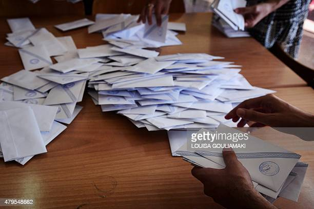 Polling station officials count the ballots at a polling station in Athens on July 5 2015 The 'No' vote was seen prevailing in Greece's referendum as...