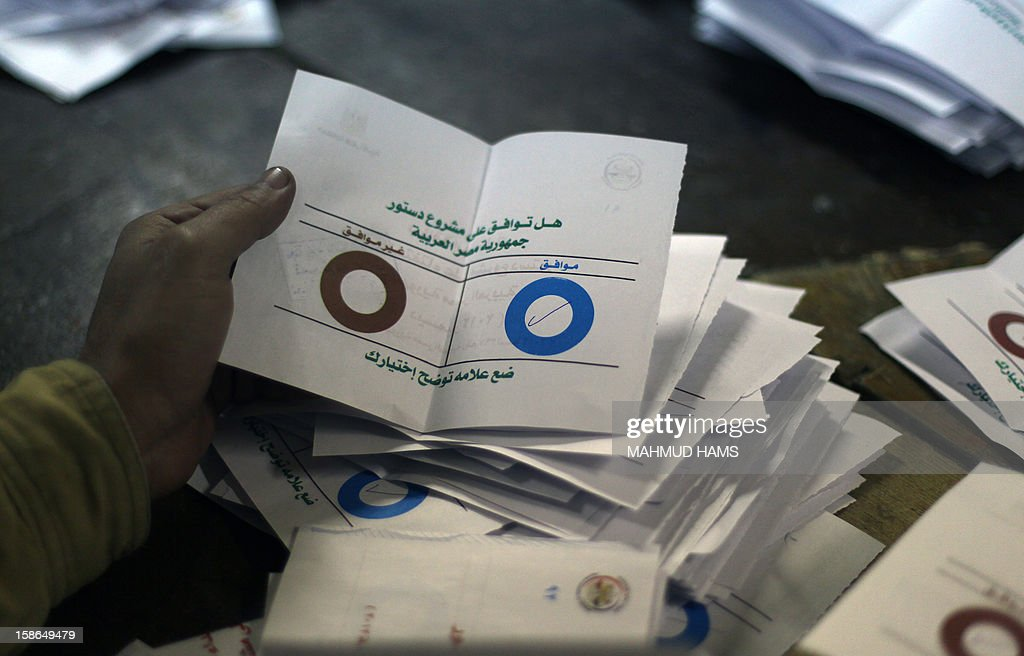 Polling station officials deposit ballots during the second round of a referendum on a new draft constitution in Giza, south of Cairo, on December 22, 2012. Egyptians are voting in the final round of a referendum on a new constitution championed by President Mohamed Morsi and his Islamist allies against fierce protests from the secular-leaning opposition.