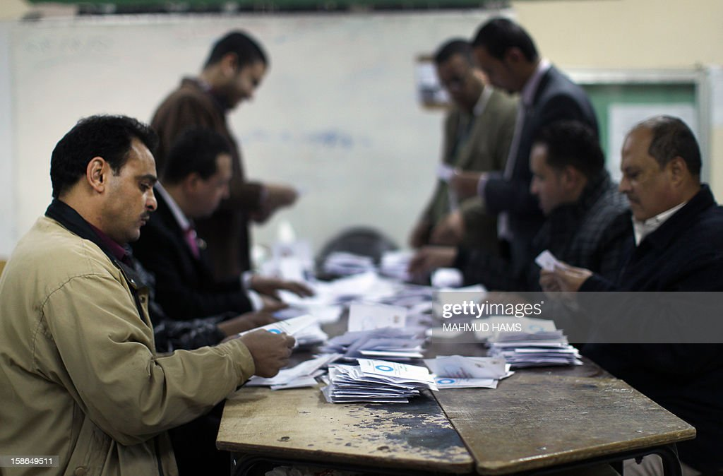 Polling station officials deposit ballots during the second round of a referendum on a new draft constitution in Giza, south of Cairo, on December 22, 2012. Egyptians are voting in the final round of a referendum on a new constitution championed by President Mohamed Morsi and his Islamist allies against fierce protests from the secular-leaning opposition. AFP PHOTO/MAHMUD HAMS