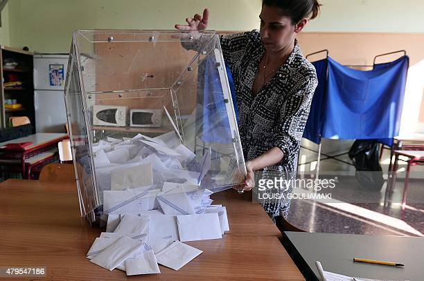 Polling station officials empty a ballot box to count the votes at a polling station in Athens on July 5 2015 The 'No' vote was seen prevailing in...