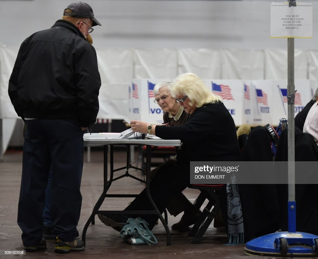 Polling station workers check in a voter at Belmont High School February 9, 2016 in Belmont New Hampshire. Voting began in New Hampshire on Tuesday in the first US presidential primary, where Donald Trump leads the packed Republican field and Bernie Sanders was polling ahead of Hillary Clinton. Despite its small size New Hampshire's spot on the electoral calendar gives it special importance in the long state-by-state battle to select the Republican and Democratic candidates who will go head to head for the White House. / AFP / Don EMMERT