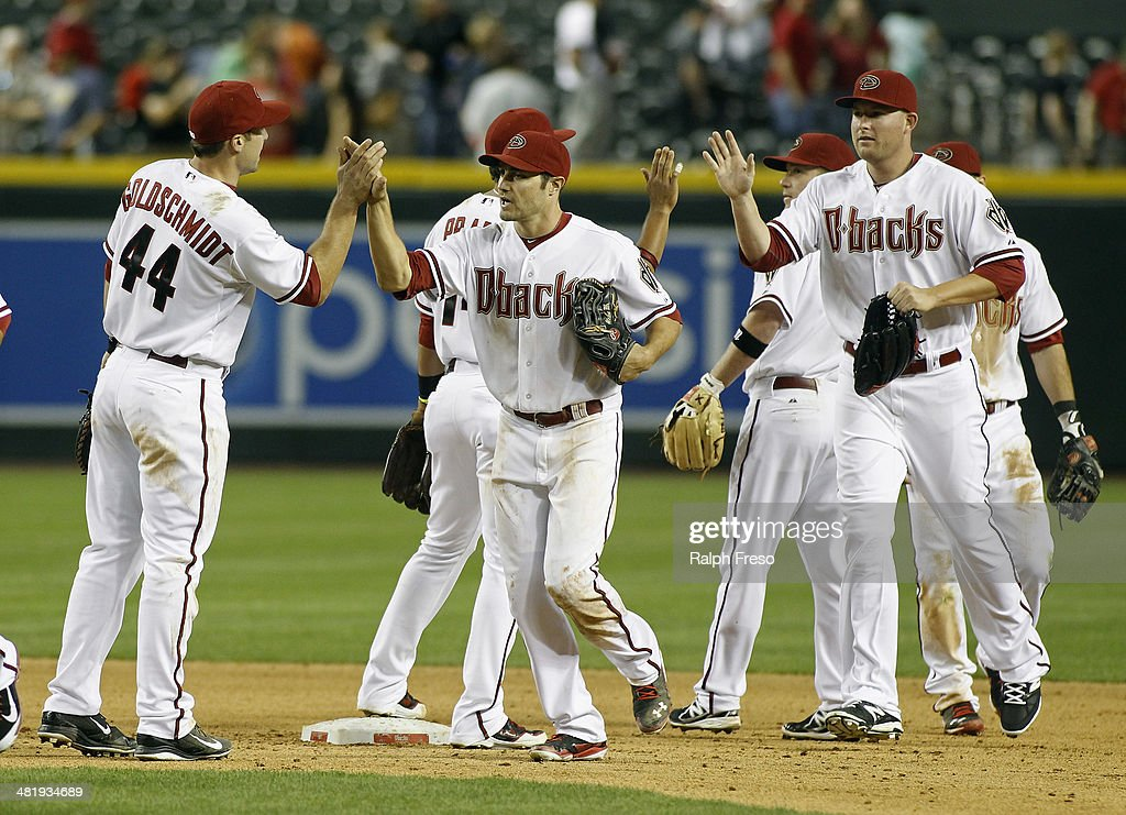 A.J. Pollock #11 (C) and <a gi-track='captionPersonalityLinkClicked' href=/galleries/search?phrase=Mark+Trumbo&family=editorial&specificpeople=4921667 ng-click='$event.stopPropagation()'>Mark Trumbo</a> #15 (R) of the Arizona Diamondbacks are congratulated by Paul Goldschmidt #44 and teammates after a 5-4 victory against the San Francisco Giants during a MLB game at Chase Field on April 1, 2014 in Phoenix, Arizona.