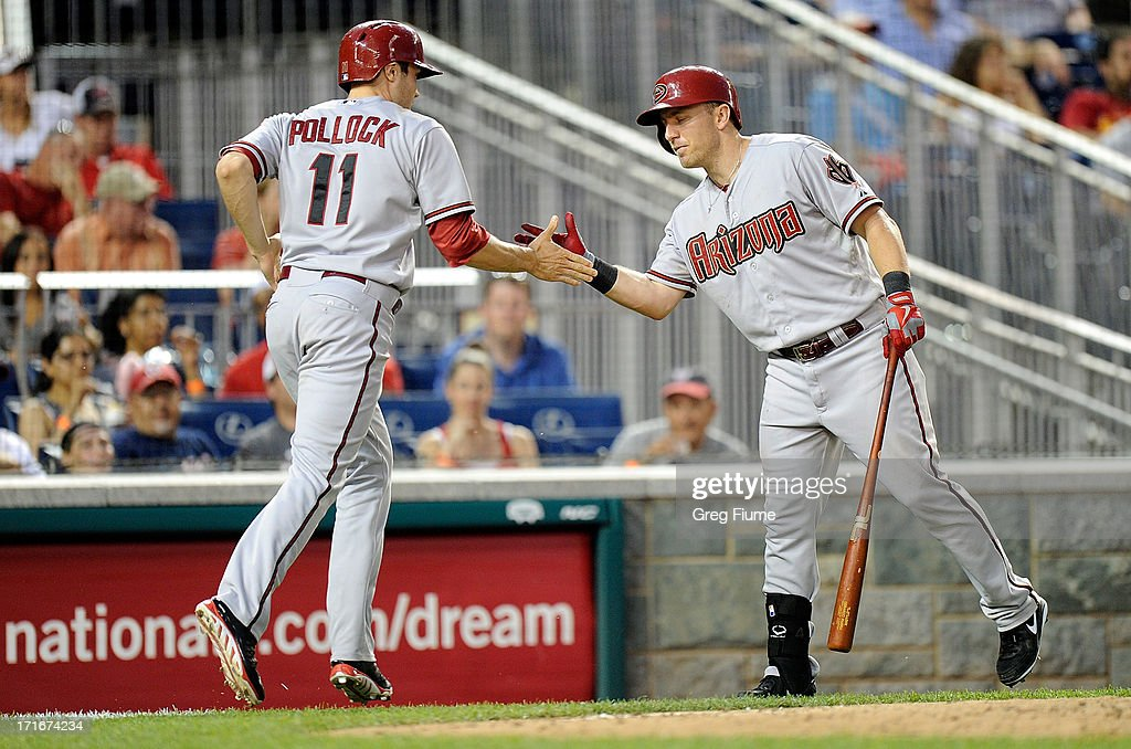 A.J. Pollock #11 of the Arizona Diamondbacks celebrates with Cliff Pennington #4 after scoring the game winning run in the eleventh inning against the Washington Nationals at Nationals Park on June 27, 2013 in Washington, DC. Arizona won the game 3-2.