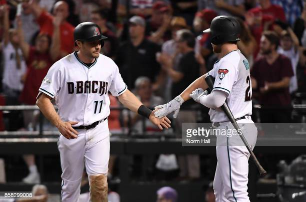 Pollock of the Arizona Diamondbacks celebrates with teammate Brandon Drury after scoring a run in the eighth inning against the Colorado Rockies...