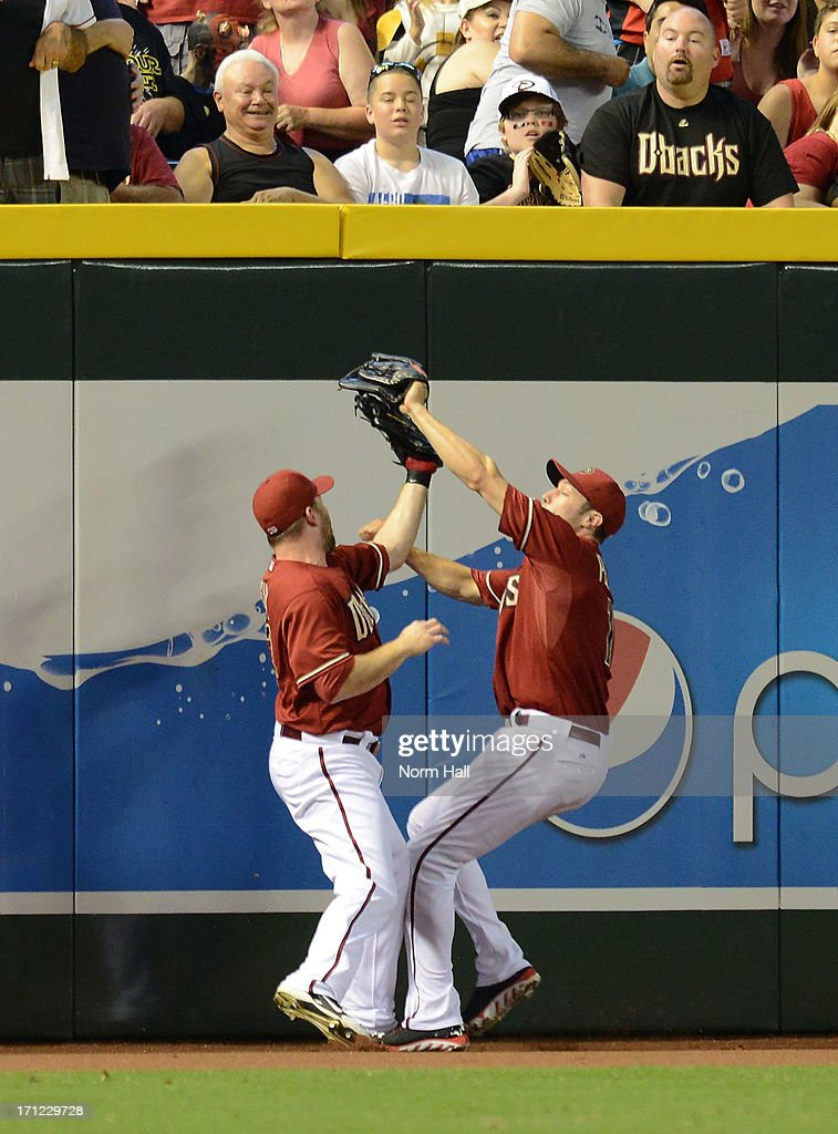 AJ Pollock #11 of the Arizona Diamondbacks comes up with a fly ball after colliding with teammate <a gi-track='captionPersonalityLinkClicked' href=/galleries/search?phrase=Jason+Kubel&family=editorial&specificpeople=575883 ng-click='$event.stopPropagation()'>Jason Kubel</a> #13 against the Cincinnati Reds at Chase Field on June 23, 2013 in Phoenix, Arizona.