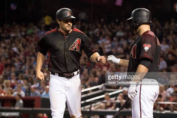J Pollock of the Arizona Diamondbacks fist bumps teammate Chris Iannetta after scoring a run during a game against the Washington Nationals at Chase...