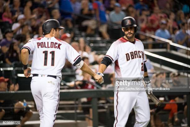 J Pollock of the Arizona Diamondbacks fist bumps teammate JD Martinez after scoring during a game against the Atlanta Braves at Chase Field on July...