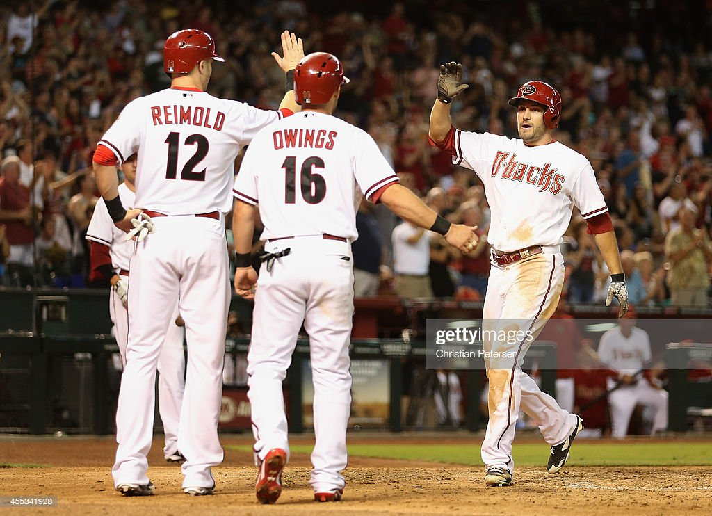 A.J. Pollock #11 of the Arizona Diamondbacks high-fives Nolan Reimold #12 and Chris Owings #16 after Pollock hit a three-run home run against the San Diego Padres during the fifth inning of the MLB game at Chase Field on September 12, 2014 in Phoenix, Arizona.