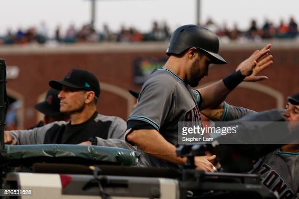 J Pollock of the Arizona Diamondbacks is being congratulated in the dugout after scoring on a triple by teammate Paul Goldschmidt during the fourth...