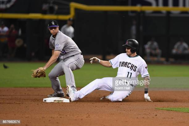 J Pollock of the Arizona Diamondbacks slides under DJ LeMahieu of the Colorado Rockies after hitting a double during the bottom of the first inning...
