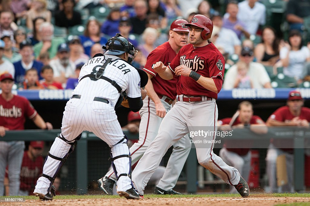 A.J. Pollock #11 of the Arizona Diamondbacks slows down before being tagged out at home plate by <a gi-track='captionPersonalityLinkClicked' href=/galleries/search?phrase=Yorvit+Torrealba&family=editorial&specificpeople=212721 ng-click='$event.stopPropagation()'>Yorvit Torrealba</a> #8 of the Colorado Rockies in the sixth inning of a game at Coors Field on September 22, 2013 in Denver, Colorado.