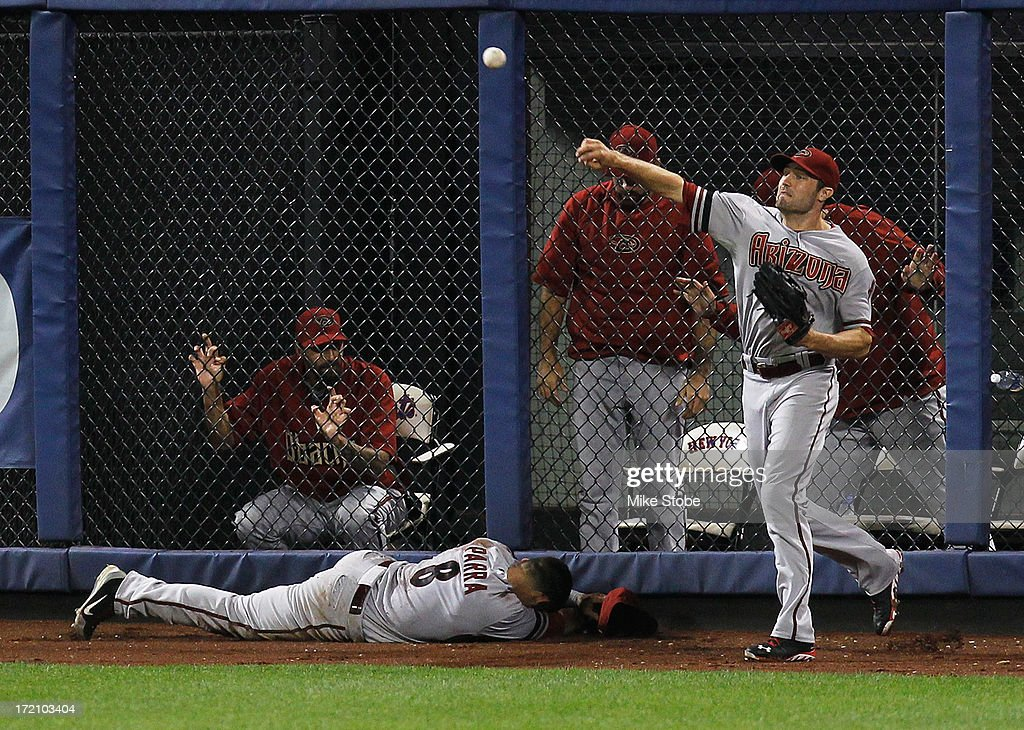 A.J. Pollock #11 of the Arizona Diamondbacks throws the ball as <a gi-track='captionPersonalityLinkClicked' href=/galleries/search?phrase=Gerardo+Parra&family=editorial&specificpeople=4959447 ng-click='$event.stopPropagation()'>Gerardo Parra</a> #8 lays on the ground injured after attempting to dive for a ball off the Omar Quintanilla #3 of the New York Mets in the eighth inning at Citi Field on July 1, 2013 at Citi Field in the Flushing neighborhood of the Queens borough of New York City.