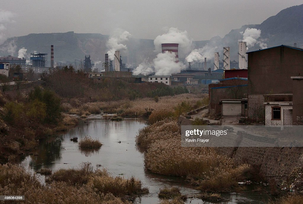 A polluted river is seen as smoke billows from smokestacks at a steel factory on November 19 2015 in the industrial province of Hebei China China's...