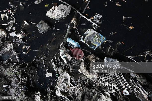 A polluted tributary of Guanabara Bay is shown littered with garbage near Rio de Janeiro on January 30 2014 in Duque de Caxias Brazil Communities...