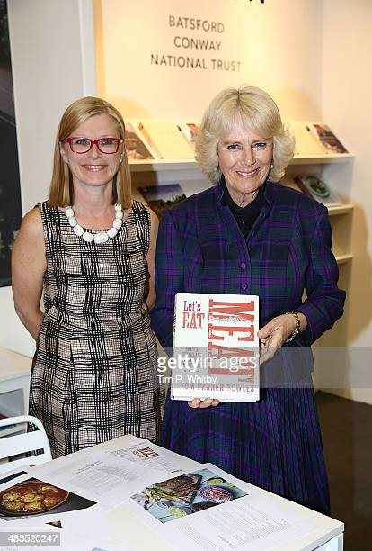 Polly Powell and Camilla Duchess of Cornwall with an advance copy of 'Lets Eat Meat' by Tom Parkerbowles during an official visit to The London Book...