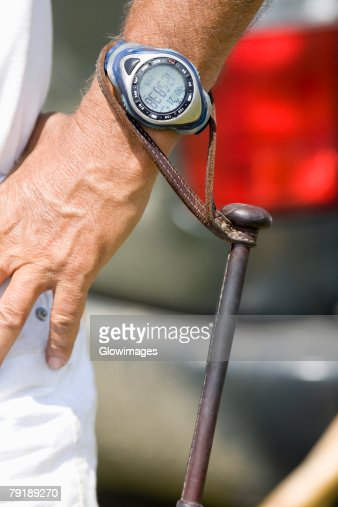 Polo mallet hanging from a wristwatch of a man : Foto de stock