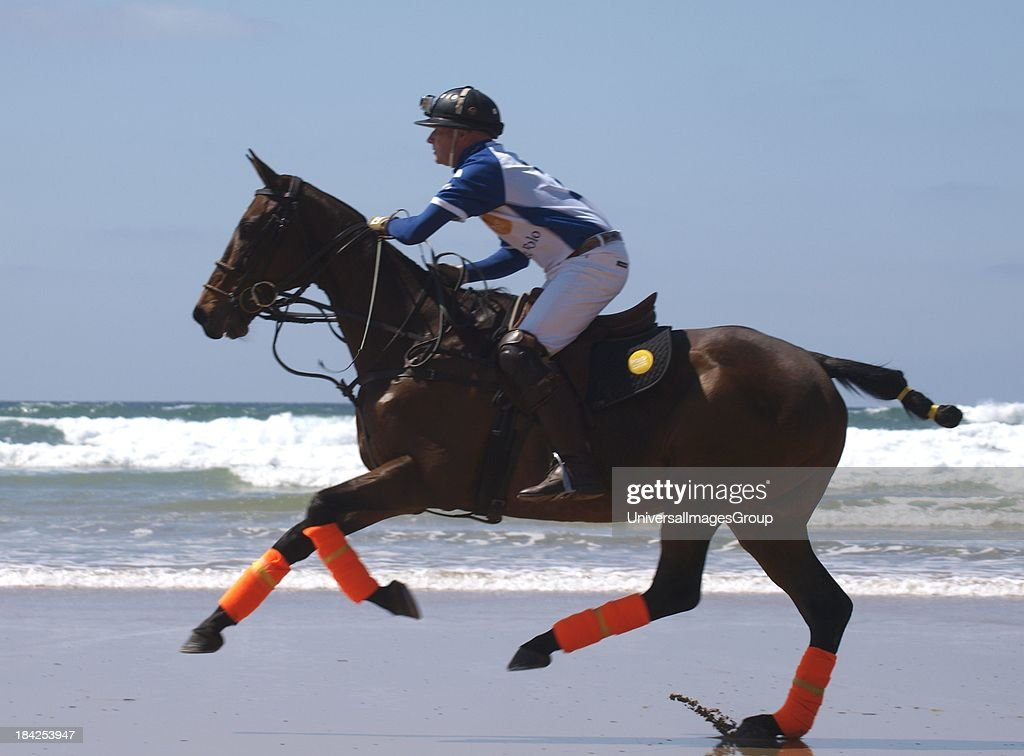 Polo player riding horse along beach, Watergate Bay, Cornwall, UK.