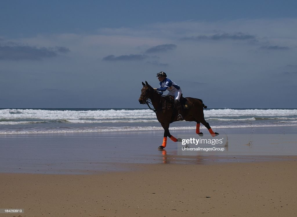 Polo player riding horse along the beach, Watergate Bay, Cornwall, UK.