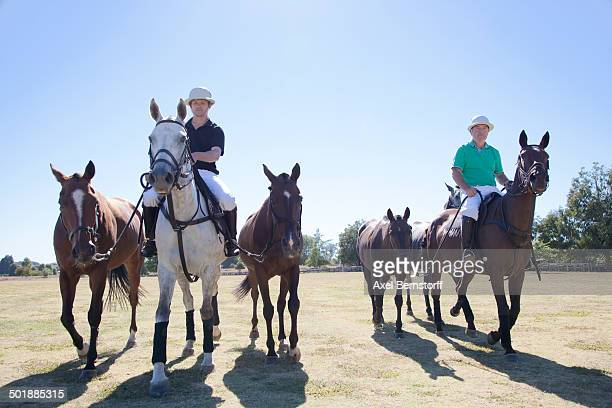 Polo players, leading horses in from field