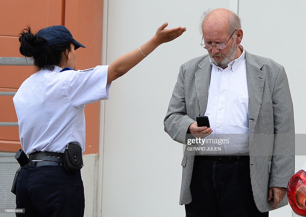 Poly Implant Prothese (PIP) founder Jean-Claude Mas (R) talks with French police woman outside the courthouse after his trial on May 17, 2013 at the Parc Chanot in Marseille, southern France, on the last day of the trial of five managers for allegedly selling faulty breast implants that sparked global health fears. PIP company was shut down on March 2010 and its product banned after it was revealed to have been using non-authorised silicone gel that caused abnormally high rupture rates of its implants. Prosecutors are pushing for a four-year sentence for the faulty breast implant firm founder. AFP PHOTO / GERARD JULIEN