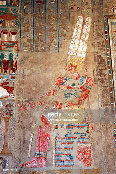 Polychrome relief depicting the god Amon sitting at a table of offerings with feather headdress beard and on both hands the scepter Uady and the ankh...