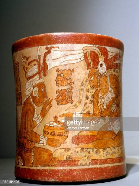 Polychrome waisted cylindrical vase with Palace Scene A dignitary seated on a box throne is attended by a male and a female servant Detail the seated...