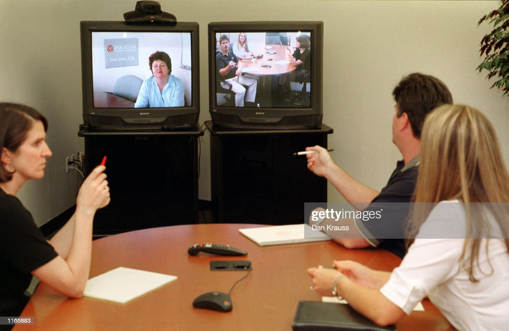 Polycom employees Lesley Philips, Kimberly Klawuhn and Victor Goodrun talk to fellow employee Alicia Morehouse October 3, 2001 on a video conferencing system at the company's Milpitas, California headquarters. The video conferencing company saw a sharp increase in demand for its products after the September 11, 2001 terrorist attacks as companies looked for an alternative to air travel.