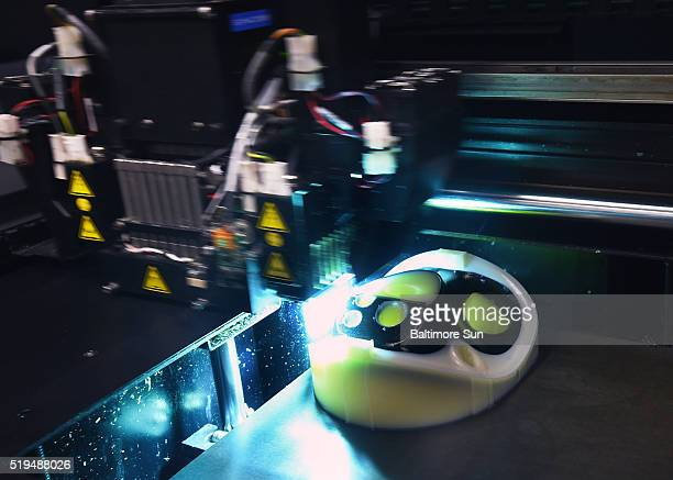 A polymer jetting machine uses the additive manufacturing process to make a prototype of a Joint Service Aircrew Mask Chem/Bio mask on March 16 2016...