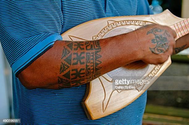 Polynesian man playing a ukulele