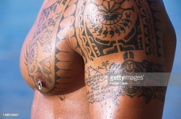 Polynesian tattoos on man's chest and arms.