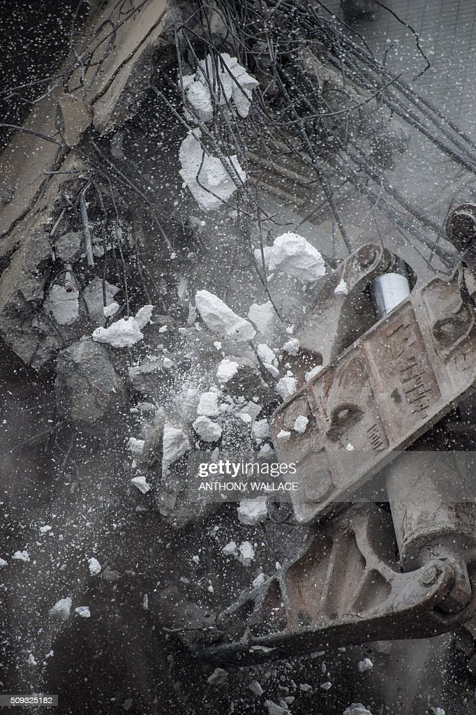 Polystyrene used at the time of construction crumbles from the structure as excavators are used during the search and rescue operation at the Wei-Kuan complex which collapsed in the 6.4-magnitude earthquake, in the southern Taiwanese city of Tainan on February 10, 2016. Taiwan prosecutors were on February 10 questioning the developer of the apartment complex that collapsed during the earthquake as prosecutors detailed flaws in construction of the building where nearly 100 people remain trapped. AFP PHOTO / ANTHONY WALLACE / AFP / ANTHONY WALLACE