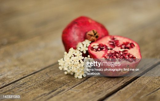 Pomegranate and flowers on tabletop : Stock Photo