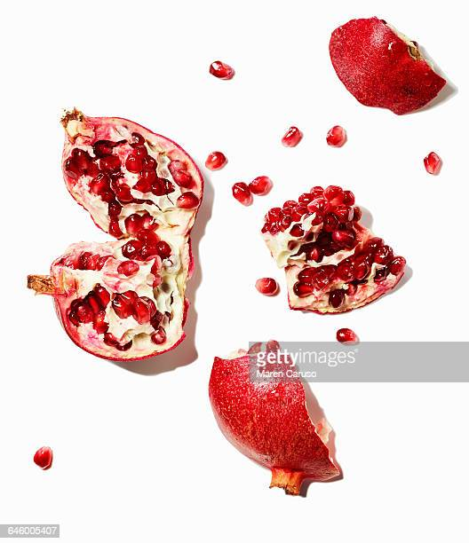 Pomegranate and seeds on white background