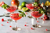 Pomegranate and basil cocktails with a twist of lime in vintage glasses on a marble countertop. It could be a pomegranate basil martini or a gin smash. Since pomegranates are widely available in the w