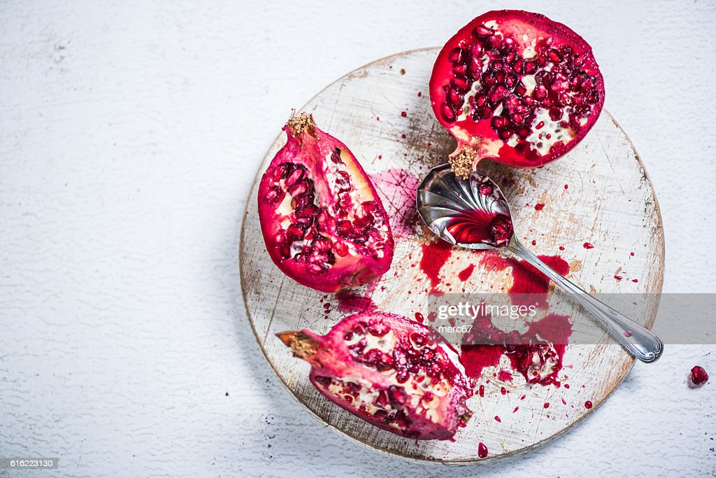 Pomegranate cut on board : Stock Photo