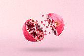 Pomegranate in flight burst. Cut half pomegranate flying in the air. Pomegranate fruit explosion.