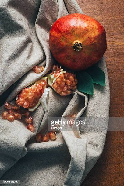 Pomegranate on linen and wood surface