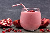 Pomegranate raspberry smoothie in a tumbler glass with pomegranate pieces, scene on black slate