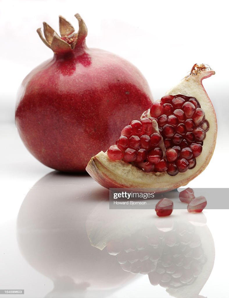 Pomegranate, with slice, on white