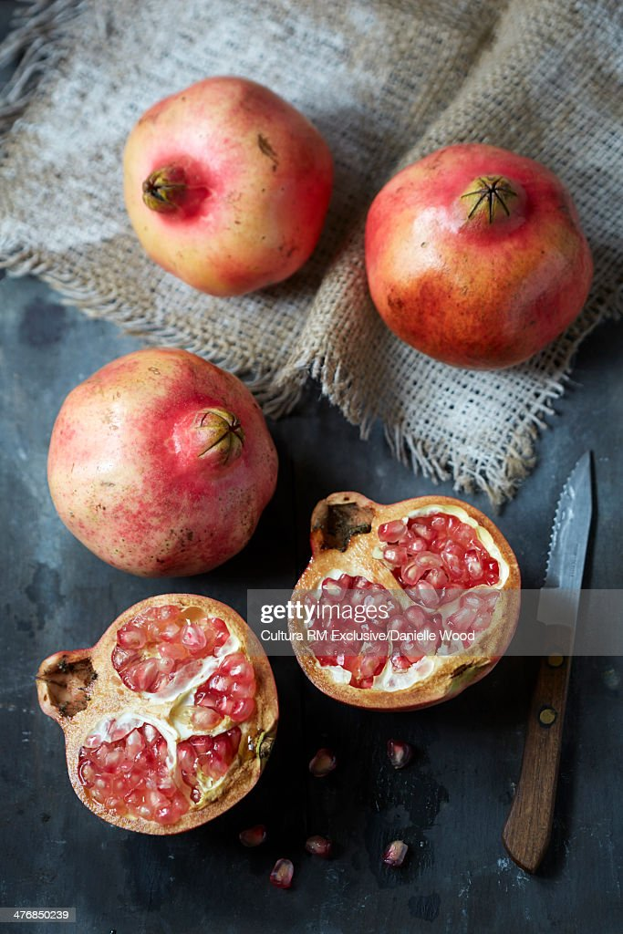 Pomegranates whole and sliced on a slate surface with kitchen knife
