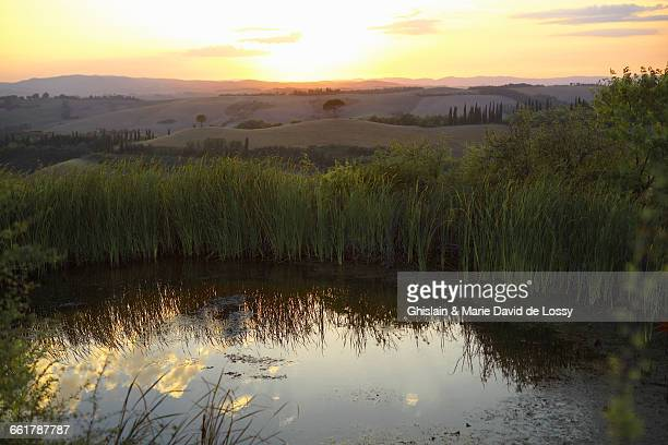 Pond and distant hilly landscape at sunrise, Tuscany, Italy